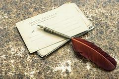 老明信片和古色古香的墨水羽毛笔 图库摄影