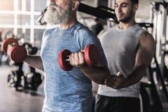 老有胡子的人有锻炼在与专业辅导员的健身房 免版税库存图片