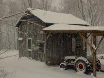 老朋友、谷仓和拖拉机在雪 库存照片