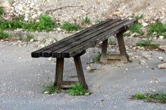 老木公开长凳有在被放弃的停车场被铺的边缘登上的强的生锈的金属支持包围与岩石 库存图片
