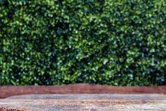 老木包伙食在bokeh自然绿色背景,透视棕色木桌前面的前面,木板条空白倒空 库存照片
