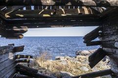 老木小屋,通过被毁坏的墙壁是可看见的岩石 免版税图库摄影