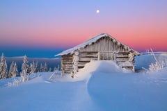 老木小屋 巨大的随风飘飞的雪 高山的背景 高fairtrees freezed与雪花 免版税库存照片
