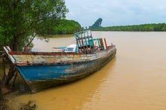 老木小船,被放弃和恶化在一条泥泞的河 免版税图库摄影