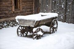 老木推车在庭院农民爱沙尼亚语村庄在雪的冬天 免版税图库摄影
