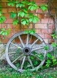 老木推车轮子对墙壁 免版税库存照片