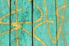 老木板条纹理与破裂的绿色和黄色油漆特写镜头的 库存照片