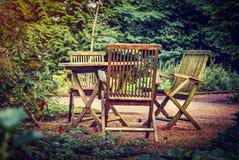 老木桌和椅子在乡间别墅绿色庭院里  假日在新鲜空气的乡下 免版税库存图片