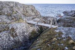 老木桥和台阶在一个岩质岛上在背景中 免版税库存图片