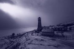 老木灯塔在冻港口边缘的夜有多云天空的 蓝色大气光 库存图片