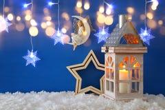 老木灯笼,雪花变成银色诗歌选光、神仙月亮的在雪和蓝色背景 库存照片