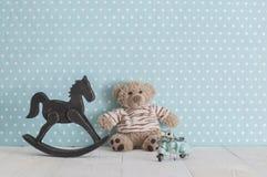 老木玩具马摇椅、玩具熊和蓝色葡萄酒 库存照片