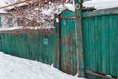 老木用雪盖的门和篱芭 免版税库存照片