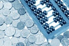老木算盘和中国硬币 免版税库存照片