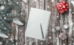 老木背景、绿色冷杉分支、白色锥体和白色装饰核桃、红色礼物和圣诞老人` s信件 免版税库存照片