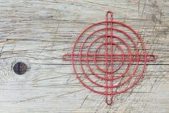 老木表面上的红色金属十字准线 库存图片
