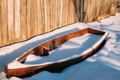 老木被放弃的划艇盖了在海岸的雪在晴朗 免版税库存图片