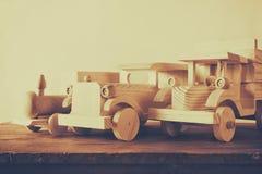 老木运输玩具:火车、汽车和轨道在木桌上 被过滤和被定调子的葡萄酒 免版税图库摄影