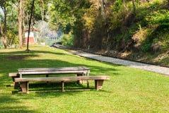 老木长凳在铁路轨道附近的公园 免版税库存图片