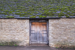 老村庄房子,有木门和青苔的盖了屋顶 库存照片