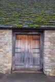 老村庄房子,有木门和青苔的盖了屋顶 免版税库存照片