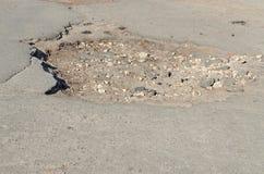 老柏油路的大坑洼 免版税库存图片