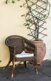 老柳条藤条椅子和花在陶瓷葡萄酒罐对黄色墙壁 免版税库存图片