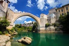 老桥梁在有鲜绿色河的Neretva莫斯塔尔 达成协议波斯尼亚夹子色的greyed黑塞哥维那包括专业的区区映射路径替补被遮蔽的状态周围的领土对都市植被 库存照片