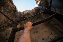 老梯子、蓝天在最后和男性手 免版税库存图片