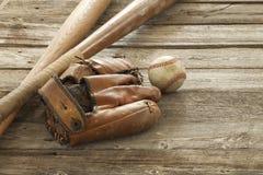 老棒球、露指手套和棒概略的木表面上 免版税库存图片