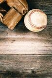 老棒球和破旧的露指手套在老木头与葡萄酒样式 免版税库存照片