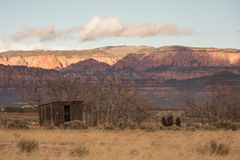 老棚子和拖拉机在冬天光秃的树中坐史密斯` s Mesa在南犹他 免版税库存图片