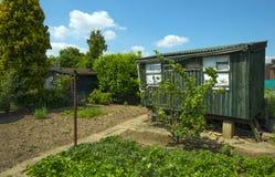 老棚子在一个晴朗的庭院里在春天 库存照片