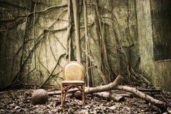 老椅子和被破坏的墙壁 库存照片