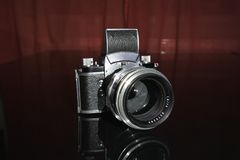 老模式手工35 mm影片的葡萄酒德国SLR照相机在与老德国画象透镜的黑背景 库存图片