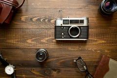 老模式照相机、透镜、笔记本和手表顶视图  免版税图库摄影