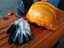 老橙色安全帽和肮脏的白色手套 免版税库存图片