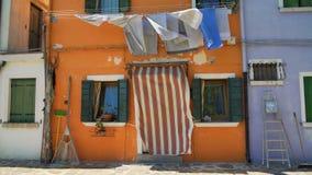 老橙色房子破旧的门面有干燥洗衣店和捕鱼设备的 影视素材