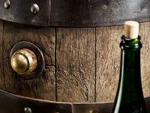 老橡木葡萄酒桶和酒瓶 图库摄影