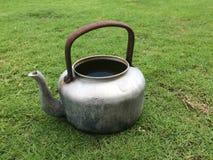 老水壶在草坪被留下 免版税库存照片