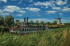 老汽船和风车在运河有灌木的和树丛在晴朗的蓝天下,在达默附近 免版税图库摄影