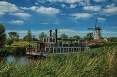 老汽船和风车在运河有灌木的和树丛在晴朗的蓝天下,在达默附近 库存图片