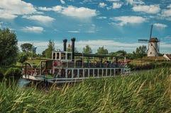 老汽船和风车在运河有灌木的和树丛在晴朗的蓝天下,在达默附近 库存照片