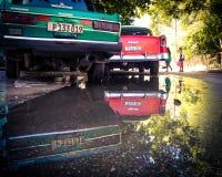 老汽车的反射在水坑的 免版税库存照片