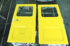 老汽车的未认出的零件在车间绘工作 免版税库存图片