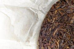 老沈puerh汉语发酵了在纸莎草纸背景的茶与copyspace 图库摄影