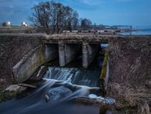 老河水坝在晚上 长的曝光弄脏的水 库存图片