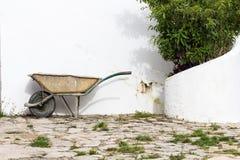 老泥泞的庭院独轮车 免版税库存照片