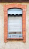 老浅兰的滑的闭合的窗口快门 红砖窗口 免版税库存照片