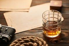 老测距仪照相机和威士忌酒与古色古香的地图 库存图片
